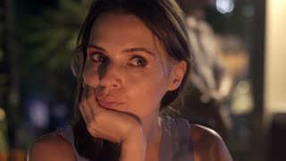 Sad, pensive woman sitting in cafe during night