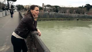 Sad pensive woman standing on the bridge by the river in city, 240fps