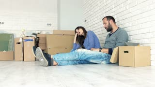 Sad, tired couple sitting on floor at their new home, 4K