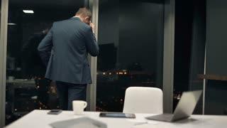 Sad, unhappy businessman walking by window
