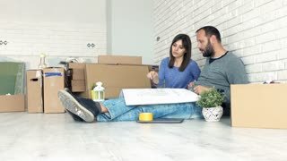 Sad, unhappy couple sitting with blueprints documents on floor at their new home 4K