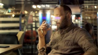 Sad, unhappy man drinking wine sitting in cafe during evening