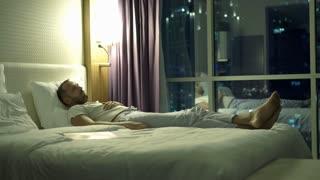 Sad, unhappy man lying on bed during night, 4K