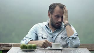 Sad, unhappy man sitting by table on terrace
