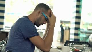 Sad, unhappy man sitting in hotel restaurant during breakfast, 4K