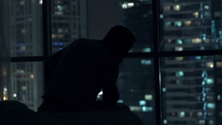Sad, unhappy man sitting on bed close to the window during night