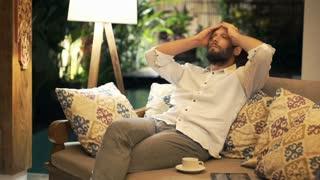 Sad, unhappy man sitting on sofa during night
