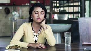 Sad, unhappy woman sitting by table at kitchen at home