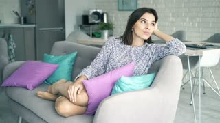 Sad unhappy woman sitting on sofa at home, 4K