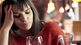 Sad, unhappy woman thinking and drinking red wine in cafe