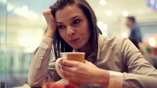 Sad woman drinking coffee at the shopping mall