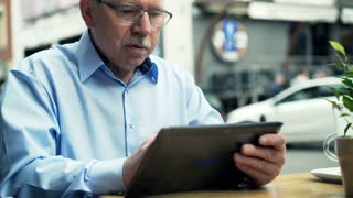 Senior man using tablet while sitting in cafe in city