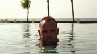 Serious man surfacing from water