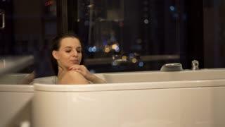 Sexy woman in bathroom washing her arms sitting in  bathtub