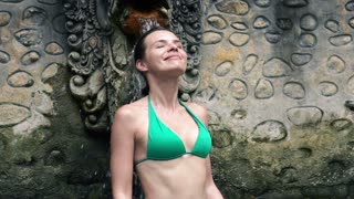Sexy woman in bikini taking bath in hot springs in bali