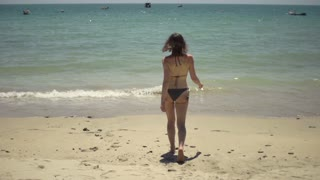 Sexy woman in bikini walking into sea, slow motion shot at 240fps