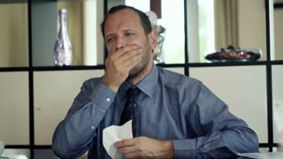 Sick young businessman blowing his nose in the office