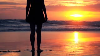 Silhouette of beautiful woman standing on the beach during sunset, super slow motion