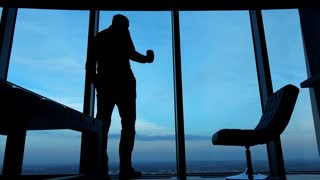 Silhouette of businessman drinking coffee while standing by window in the evening, 4K