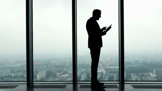 Silhouette of businessman standing with smartphone by window in the office, 4K
