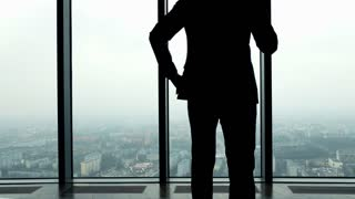 Silhouette of businessman talking on cellphone, standing by the window in the office, 4K