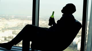 Silhouette of drunk man drinking wine on armchair by the window