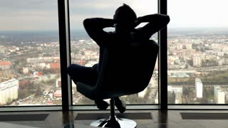 Silhouette of happy man touring round on the armchair in the office, super slow motion
