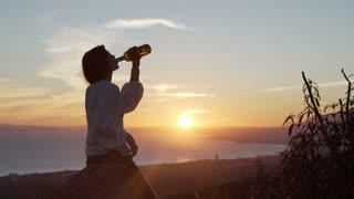 Silhouette of happy woman drinking wine during sunset in the country