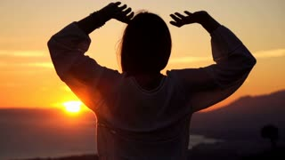 Silhouette of happy woman raising arms on the beach during sunset super slow motion