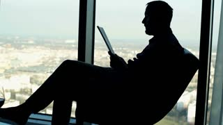 Silhouette of man reading magazine sitting on chair at home by the window