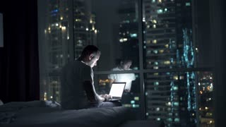 Silhouette of man using laptop and falling asleep on bed at night at home, 4K