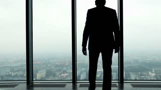 Silhouette of successful businessman raising arms, power symbol, in the office, 4K