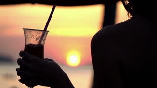 Silhouette of woman holding cocktail on sunbed during sunset, slow motion 240fps