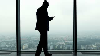Silhouette of young businessman standing with tablet computer by in the office, 4K