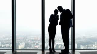 Silhouette of young businesspeople with smartphone by the window in the office, 4K