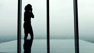 Silhouette of young businesswoman talking on cellphone standing by window in the office, 4K