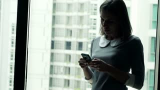 Silhouette of young businesswoman texting on smartphone standing by the window in the city