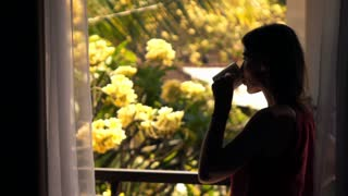 Silhouette of young, happy woman drinking water on terrace during sunny day, super slow motion
