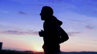 silhouette of young man jogging during sunset