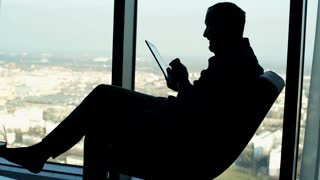 Silhouette of young man using tablet computer sitting on armchair by the window