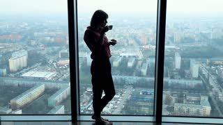 Silhouette of young, pensive woman drinking coffee and admire view from window, super slow motion