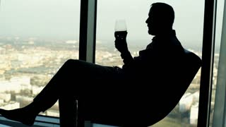 Silhouette of young sad, lonely man shaking wine on armchair close to the window