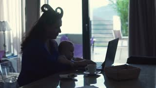 Silhouette of young, tired mother  trying work on laptop with her little child