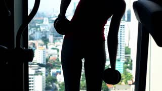 Silhouette of young woman doing exercise with dumbbell on the gym, super slow motion, 120fps