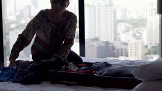 Silhouette of young woman packing suitcase in hotel room