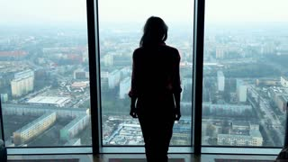 Silhouette of young woman walking and admire city view from the window, super slow motion