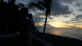 Silhouette woman taking photo with cellphone during sunset on the beach, super slow motion