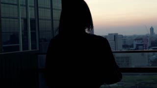 Silhouette young woman in bathrobe admire city view from terrace