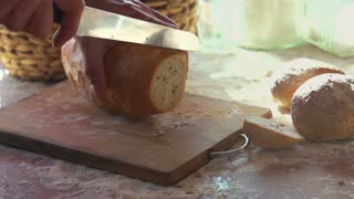 Slicing fresh, crusty bread on chopping board super slow motion, shot at 240fps