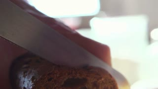 Slicing fresh, dark, whole grains bread on wooden table super slow motion